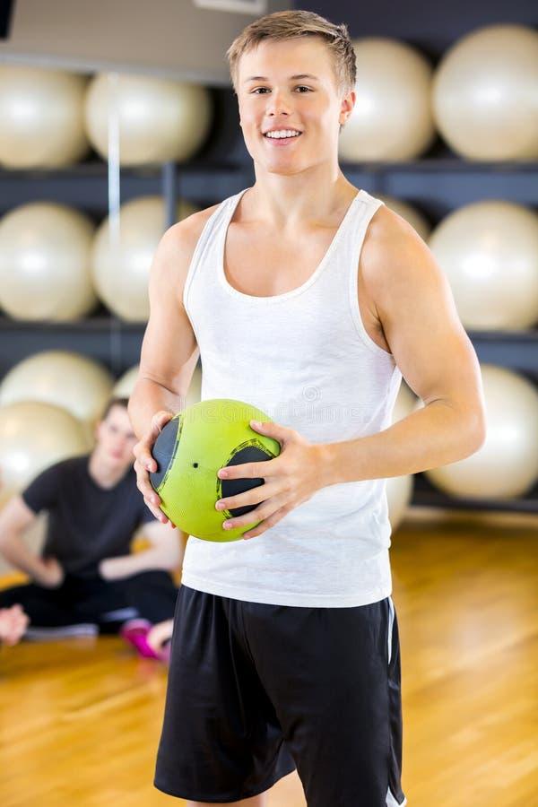 Hombre joven sonriente que sostiene una bola del golpe en el gimnasio de la aptitud imagenes de archivo