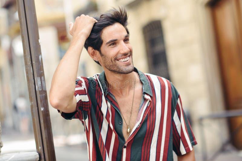 Hombre joven sonriente que toca su pelo que lleva la ropa casual al aire libre imagen de archivo libre de regalías