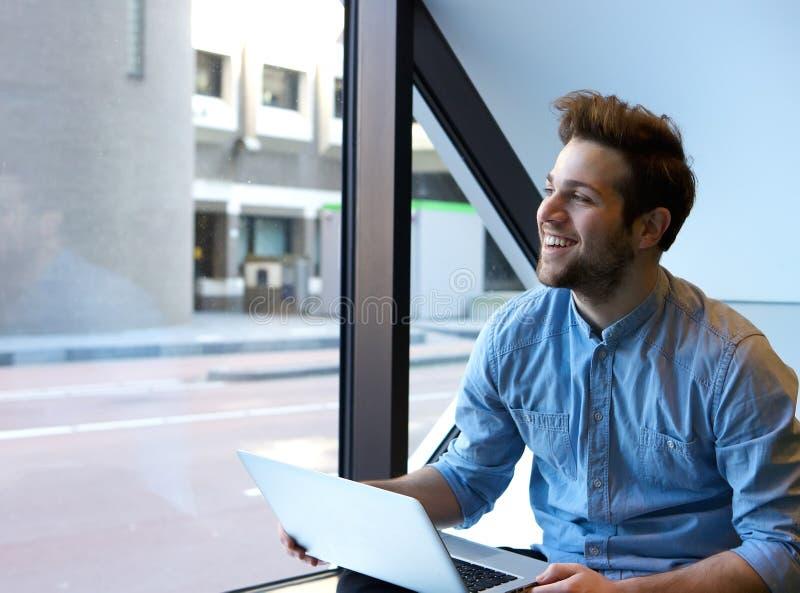 Hombre joven sonriente que usa la computadora portátil imagen de archivo