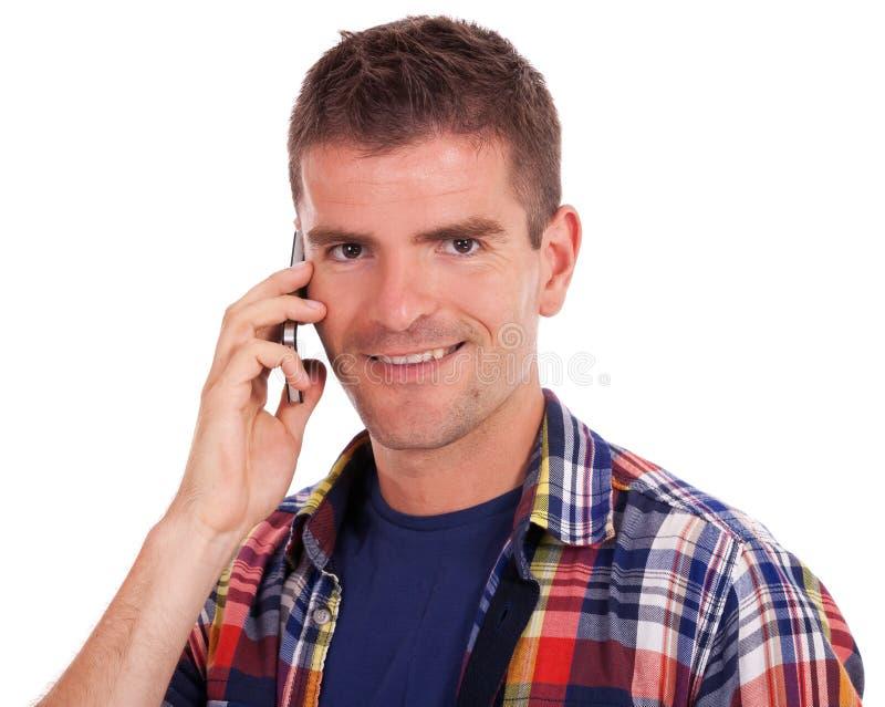 Hombre joven sonriente que usa su teléfono foto de archivo libre de regalías
