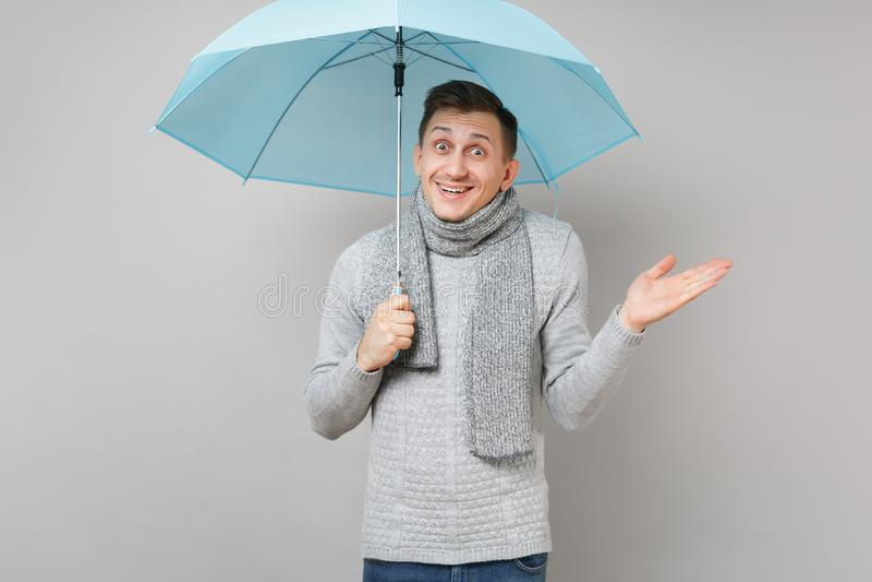 Hombre joven sorprendente en el suéter gris, bufanda señalando, paraguas azul de extensión de la tenencia de la mano aislado en f foto de archivo libre de regalías