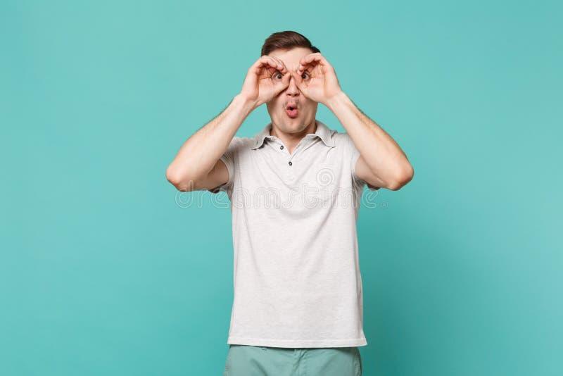 Hombre joven sorprendente en la ropa casual que lleva a cabo las manos cerca de ojos, imitando los vidrios o los prismáticos aisl imágenes de archivo libres de regalías