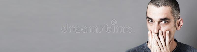 Hombre joven sorprendente que oculta su boca para el miedo, bandera gris foto de archivo
