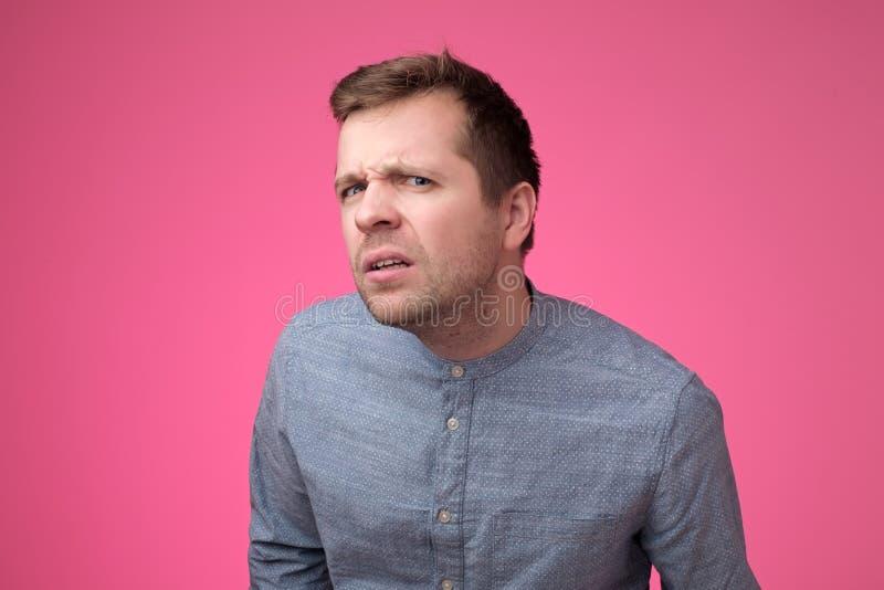 Hombre joven sorprendente y chocado que oye malas noticias, siendo dudoso sobre la pared rosada fotos de archivo