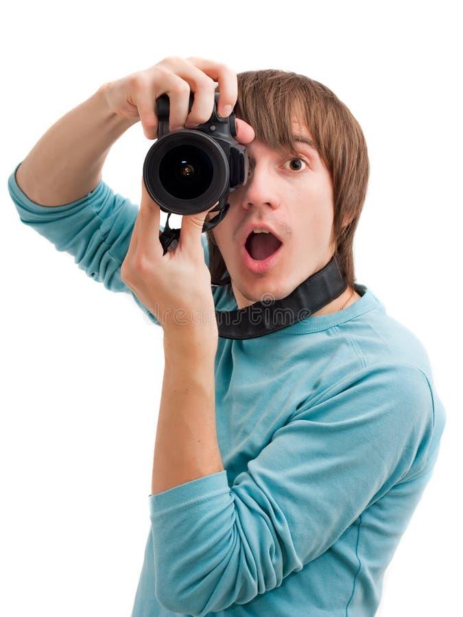 Hombre joven sorprendido con la cámara de la foto imagen de archivo