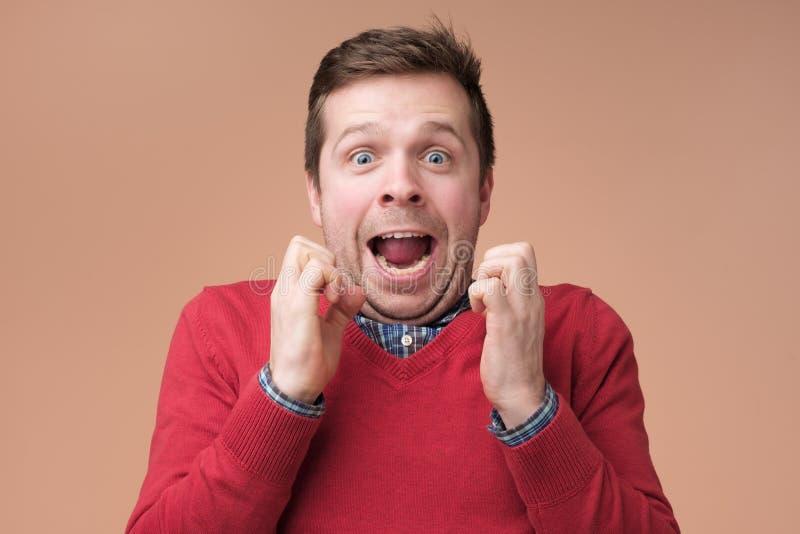 Hombre joven sorprendido emocionado en el suéter rojo que guarda las caras de los athis de los puños apretados, chocadas fotografía de archivo libre de regalías