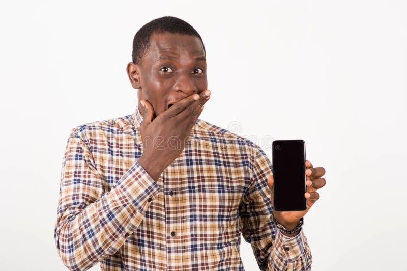 Hombre joven sorprendido mostrando la pantalla negra del teléfono elegante imágenes de archivo libres de regalías