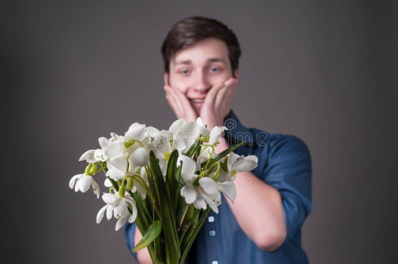Hombre joven sorprendido y sonriente hermoso en la camisa azul que toca mejillas y que mira el ramo de snowdrops en fondo gris imágenes de archivo libres de regalías