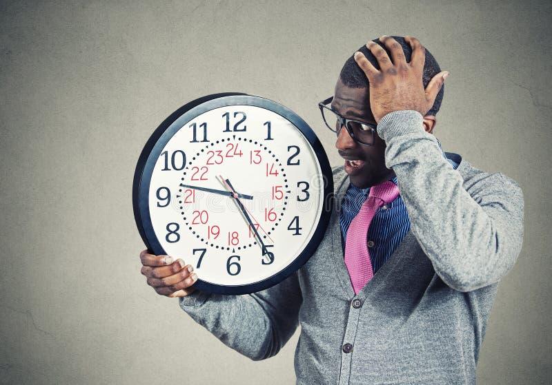 Hombre joven subrayado que corre del tiempo que mira el reloj de pared fotos de archivo libres de regalías