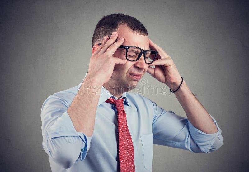 Hombre joven subrayado que tiene dolor de cabeza imagenes de archivo