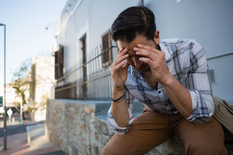 Hombre joven tensado con la cabeza en las manos que se sientan en muro de contención fotografía de archivo libre de regalías