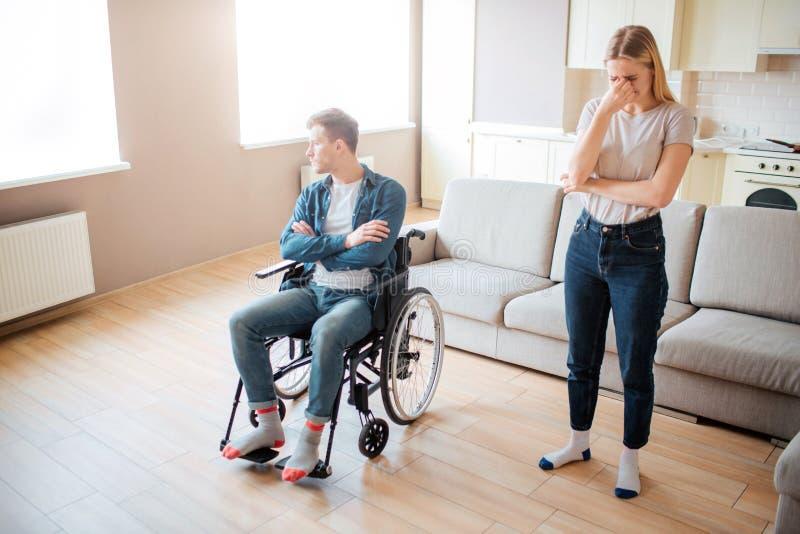 Hombre joven trastornado con incapacidad en la silla de ruedas Persona con necesidades psecial Las manos cruzaron y mirando la ve fotos de archivo