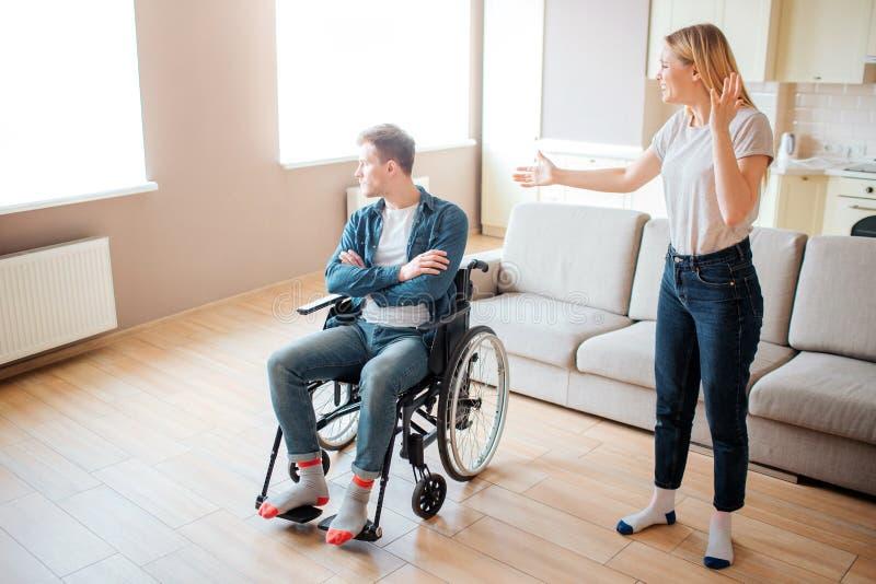Hombre joven trastornado en mirada de la silla de ruedas en ventana Individuo con necesidades e incapacidad especiales Soporte de fotografía de archivo