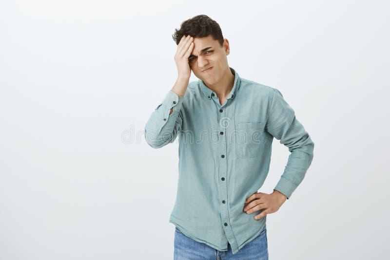 Hombre joven trastornado preocupado en la camisa sport, llevando a cabo la mano en la frente y haciendo muecas del pesar, olvidan imagenes de archivo