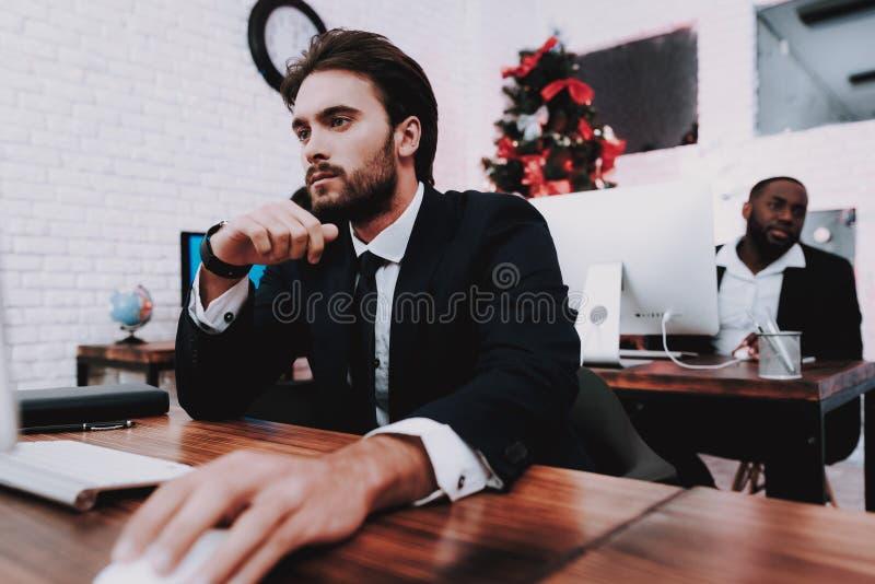 Hombre joven trastornado que trabaja en oficina en Noche Vieja fotos de archivo