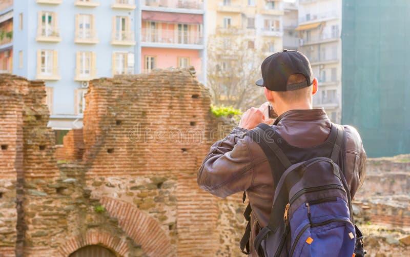 Hombre joven, turista, con la mochila, imagen en un smartphone el palacio de Galerius en la puesta del sol fotos de archivo