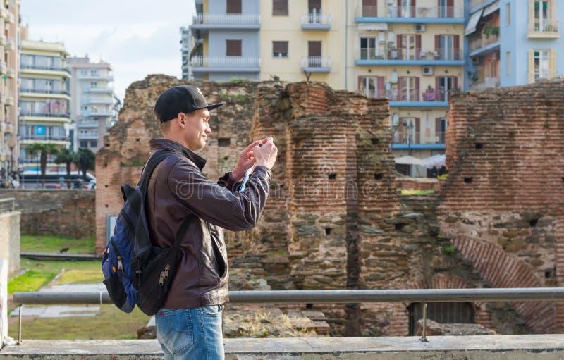 Hombre joven, turista, con la mochila tomando a imagen en un smartphone el palacio de Galerius foto de archivo