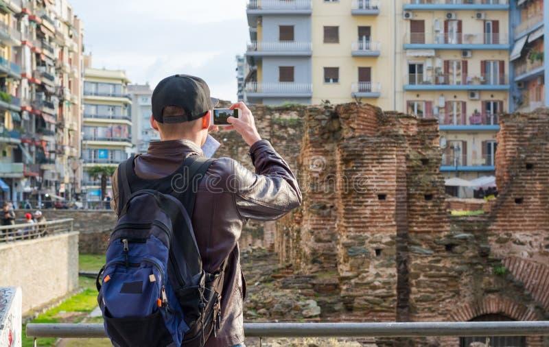 Hombre joven, turista, con la mochila tomando a imagen en un smartphone el palacio de Galerius en Salónica, Grecia imagen de archivo