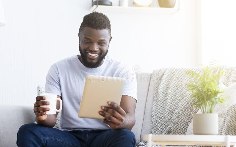 Hombre joven usando la tableta, teniendo charla video foto de archivo libre de regalías