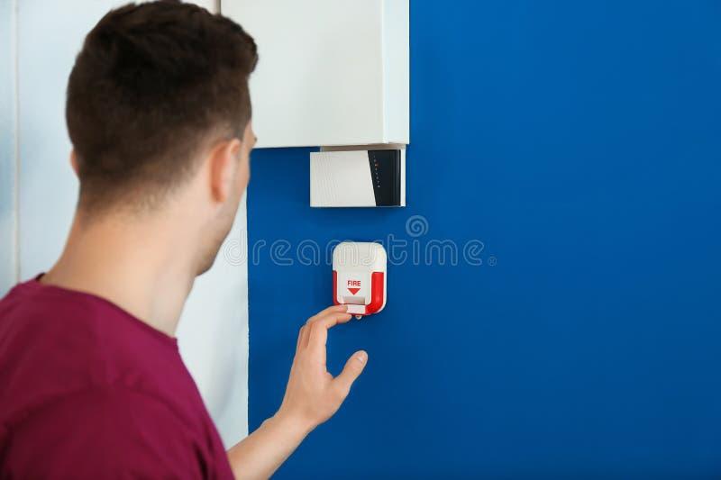 Hombre joven usando sistema alarma de incendio dentro fotografía de archivo