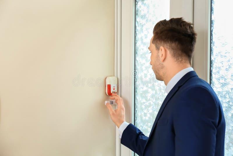 Hombre joven usando sistema alarma de incendio dentro imagenes de archivo