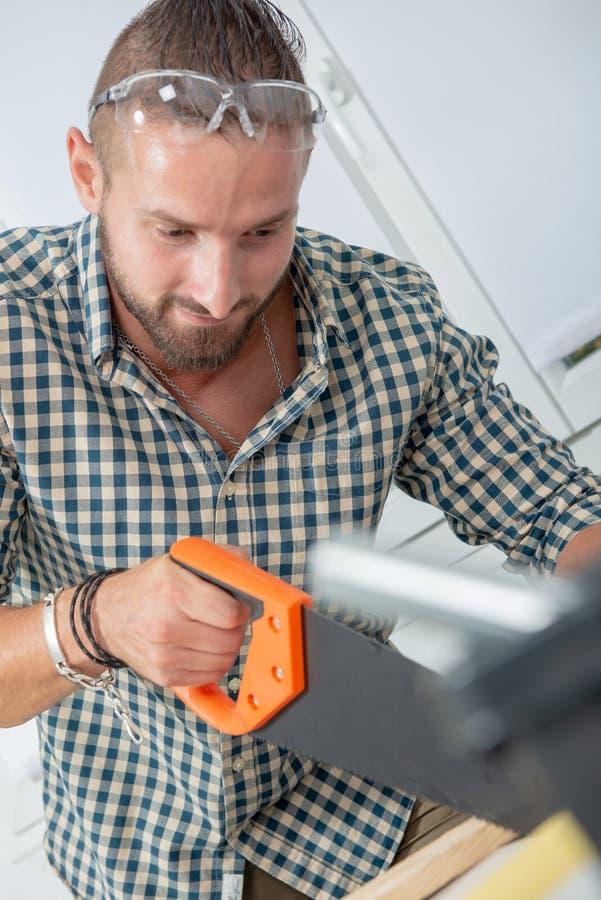 Hombre joven usando un handsaw foto de archivo libre de regalías