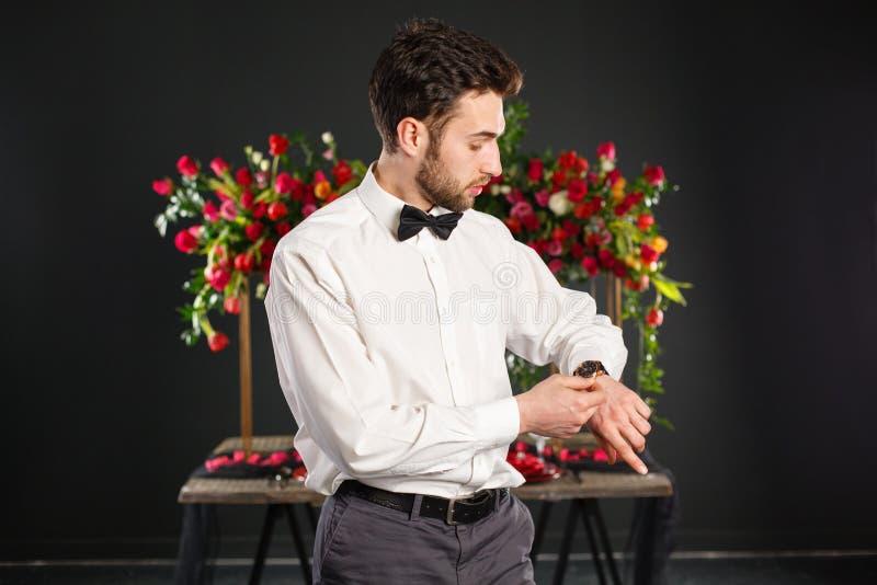 Hombre joven weared en obra clásica cerca de la tabla adornada con las flores rojas foto de archivo libre de regalías