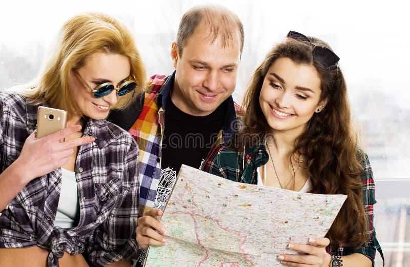 Hombre joven y dos mujeres que miran un mapa europeos americanos Recolectado en un paseo guiado Primer foto de archivo
