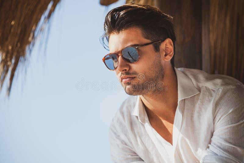 Hombre joven y hermoso con la mirada de las gafas de sol imagen de archivo