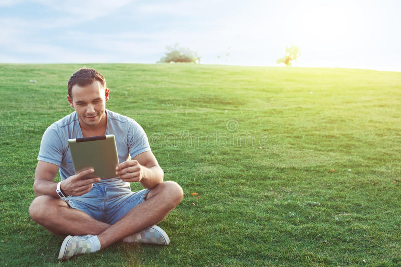 Hombre joven y hermoso con la tableta móvil imagenes de archivo