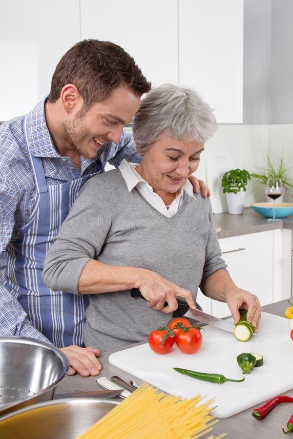 Hombre joven y más vieja mujer que cocinan junto en la cocina fotos de archivo