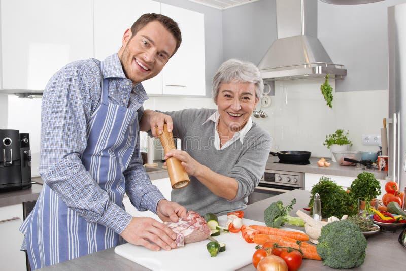 Hombre joven y más vieja mujer que cocinan junto en la cocina imagen de archivo