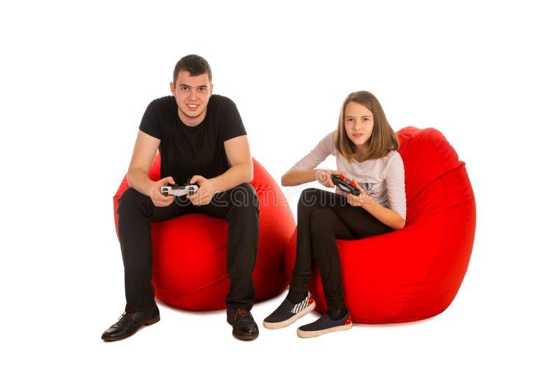 Hombre joven y muchacha divertida que juegan a los videojuegos mientras que se sienta en el re imagen de archivo libre de regalías