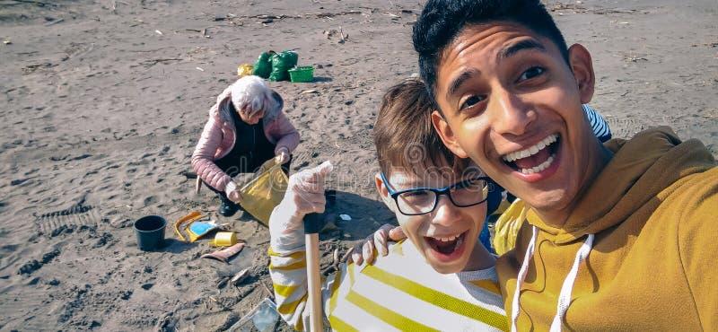 Hombre joven y muchacho que toman el selfie mientras que grupo de voluntarios que limpian la playa imagen de archivo