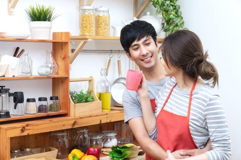 Hombre joven y mujer asiáticos atractivos de los pares que miran uno a en cocina Forma de vida asiática casada de los jóvenes en  imagenes de archivo