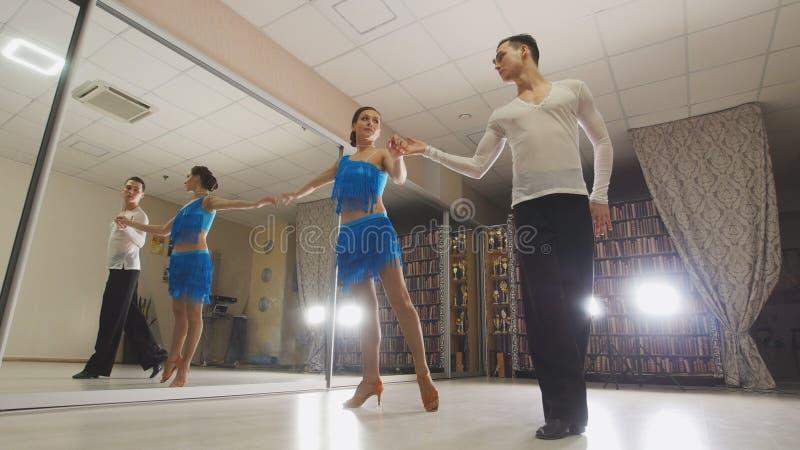 Hombre joven y mujer atractivos que bailan la danza latinoamericana en trajes en el estudio, cámara lenta, cierre para arriba, en fotografía de archivo