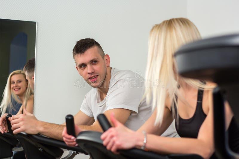 Hombre joven y mujer biking en el gimnasio, ejercitando las piernas que hacen las bicis de ciclo del entrenamiento cardiio imagen de archivo libre de regalías