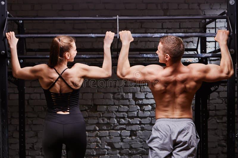 Hombre joven y mujer caucásicos atractivos del crossfit que se resuelven en el gimnasio, vista posterior, par fotos de archivo