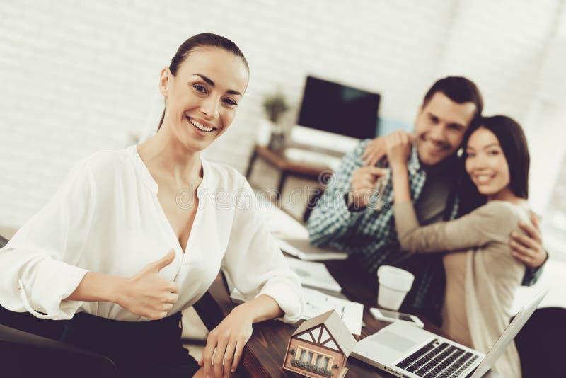 Hombre joven y mujer con agente inmobiliario sonriente en oficina imagenes de archivo