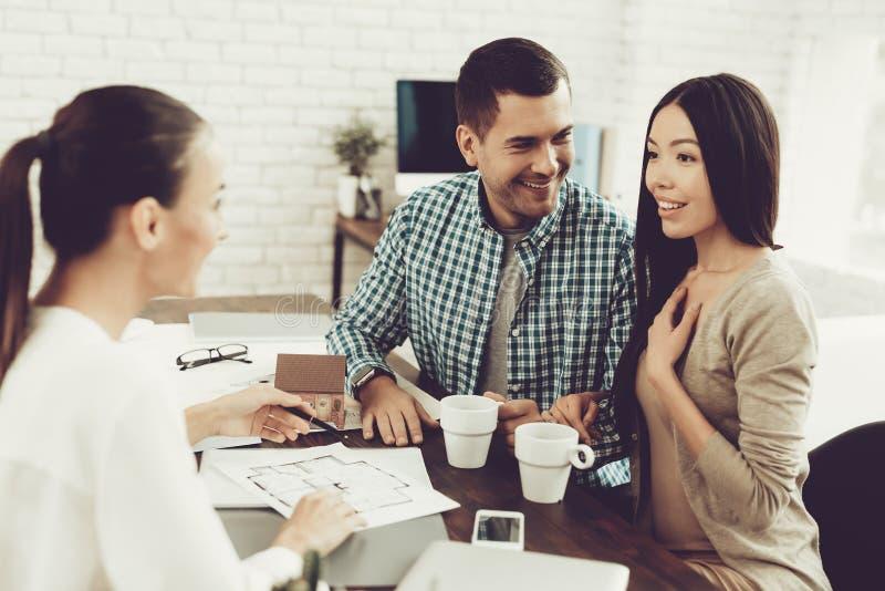 Hombre joven y mujer con agente inmobiliario sonriente en oficina imagen de archivo