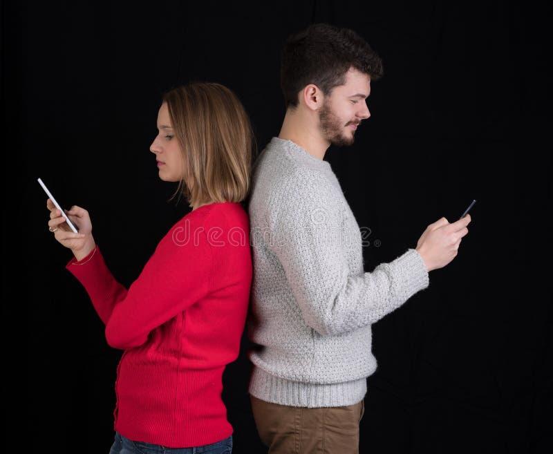 Hombre joven y mujer con los teléfonos móviles foto de archivo