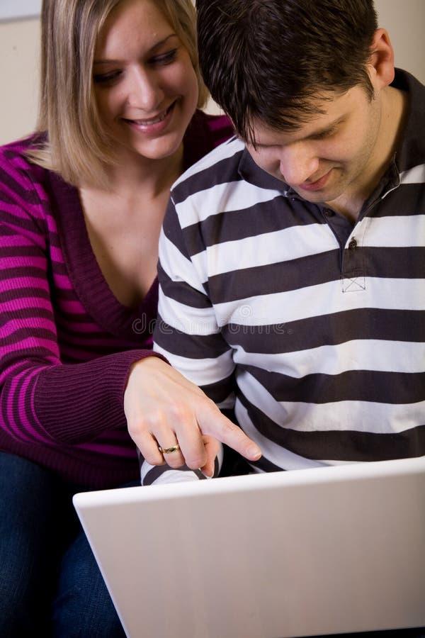 Hombre joven y mujer con un ordenador portátil blanco foto de archivo libre de regalías