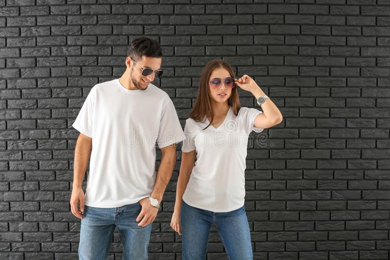 Hombre joven y mujer en camisetas elegantes contra la pared de ladrillo oscura imagen de archivo libre de regalías