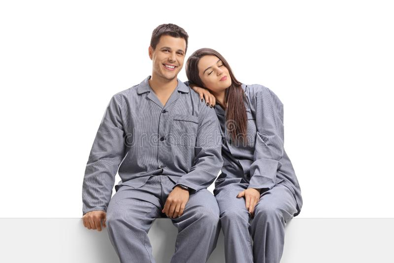 Hombre joven y mujer en los pijamas que se sientan en un panel fotografía de archivo