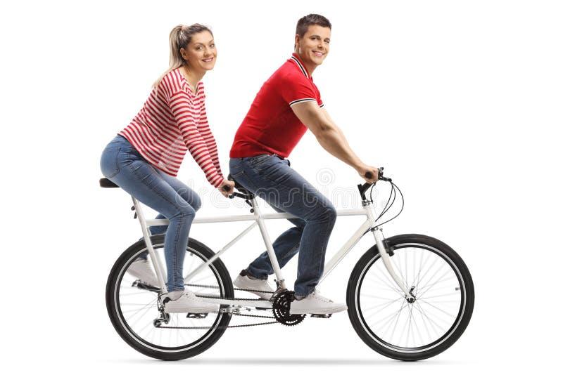 Hombre joven y mujer en una bicicleta en tándem que mira la cámara foto de archivo libre de regalías