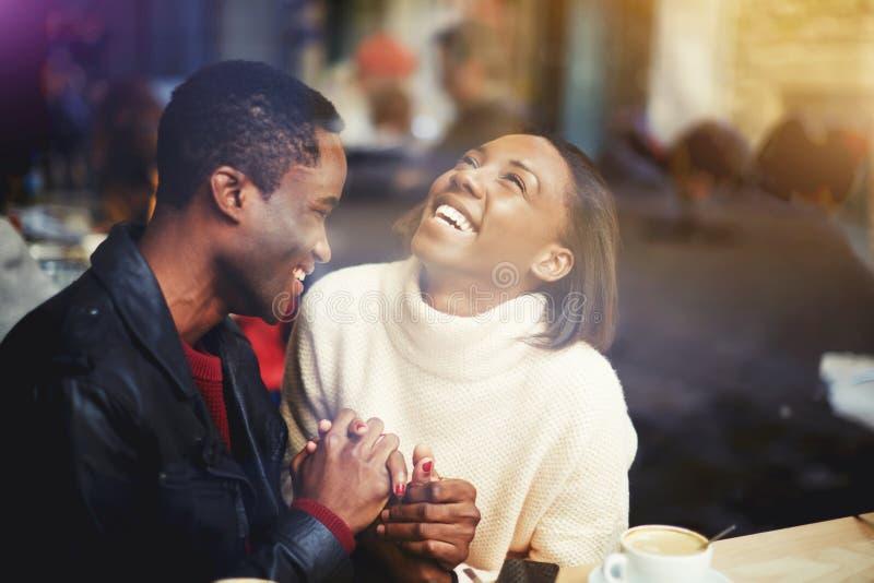 Hombre joven y mujer felices que ríen junta mientras que se sienta en restaurante moderno durante descanso para tomar café, foto de archivo