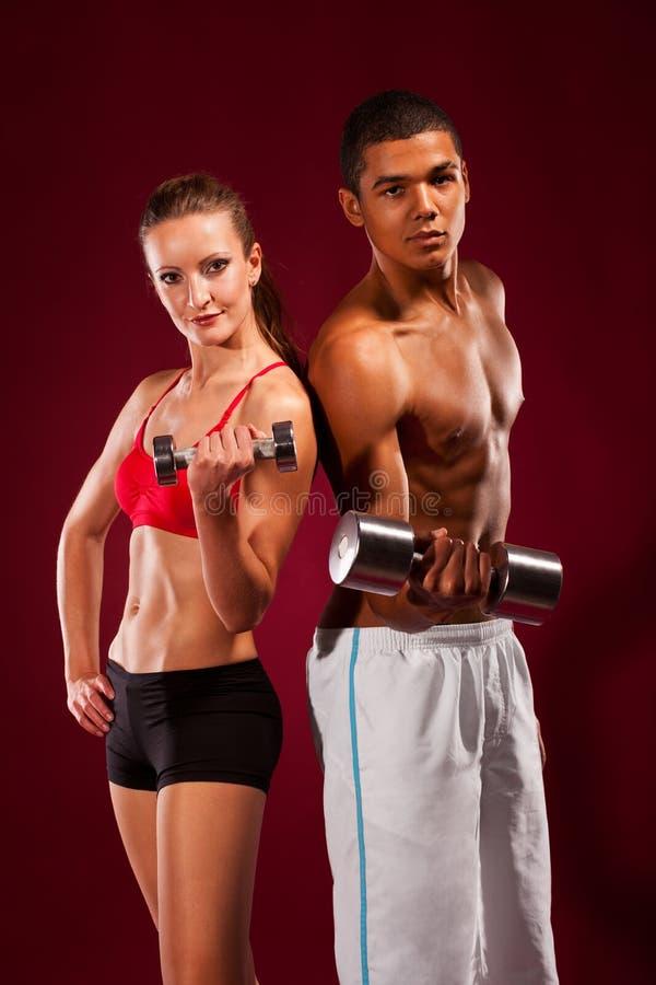 Hombre joven y mujer fuertes con pesas de gimnasia fotos de archivo libres de regalías