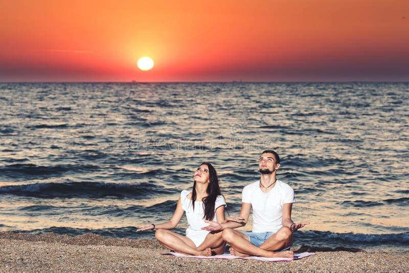 Hombre joven y mujer hacer yoga y reflexionar sobre la playa en el amanecer Concepto sano de la forma de vida imagenes de archivo