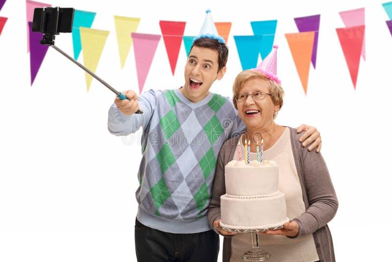 Hombre joven y mujer madura con la torta de cumpleaños que toma un selfie fotografía de archivo