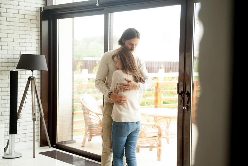 Hombre joven y mujer que abrazan la colocación en casa, reconcilia de los pares fotos de archivo